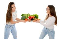 拿着篮子的两个微笑的女孩有很多菜 图库摄影