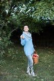 拿着篮子的妇女有很多苹果 免版税库存图片