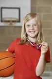 拿着篮球和奖牌在学校健身房的女孩 免版税库存照片