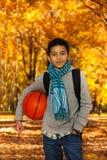 拿着篮球球的男孩外面 免版税库存照片