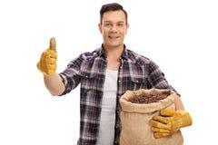 拿着粗麻布大袋用咖啡和给赞许的男性农夫 免版税库存照片