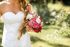 拿着精美婚姻花束的新娘 美好的晴天在公园 库存照片
