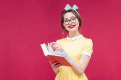 拿着红色书的玻璃的微笑的逗人喜爱的画报女孩 库存图片