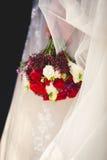 拿着红色和白玫瑰的婚礼花束新娘 免版税库存图片