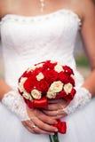 拿着红色和白玫瑰的精采花束新娘 免版税图库摄影