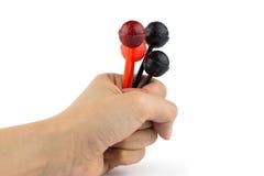 拿着红色和黑棒棒糖的手 免版税库存照片