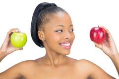 拿着红色和绿色苹果的可爱的妇女看红色一个 免版税库存照片