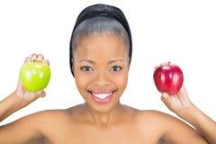拿着红色和绿色苹果的微笑的妇女看照相机 免版税图库摄影