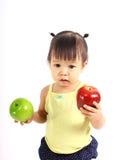 拿着红色和绿色苹果的逗人喜爱的女孩 免版税库存照片