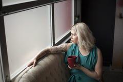 拿着红色咖啡杯的美丽的少妇 免版税库存图片