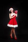 拿着红色圣诞树球的微笑的女孩 礼服和圣诞老人` s帽子的妇女 辅助工s圣诞老人 圣诞老人的h可爱的愉快的女孩 库存图片