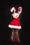 拿着红色圣诞树球的微笑的女孩 礼服和圣诞老人` s帽子的妇女 辅助工s圣诞老人 圣诞老人的h可爱的愉快的女孩 免版税库存图片