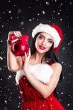 拿着红色圣诞树球的微笑的女孩 礼服和圣诞老人` s帽子的妇女 辅助工s圣诞老人 圣诞老人的h可爱的愉快的女孩 免版税库存照片