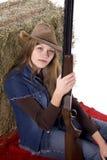 拿着红色坐的妇女的一揽子枪 免版税库存图片