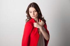 拿着红色夹克的年轻美丽的妇女 免版税图库摄影