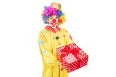 拿着红色存在的一个愉快的男性小丑 库存照片