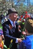 拿着红色康乃馨的退役军人的画象开花 免版税库存图片