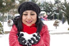 拿着红色心脏和庆祝情人节有多雪的背景的黑发土耳其妇女在她的手上 免版税库存图片