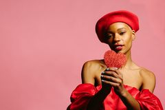 拿着红色心脏和微笑对照相机的美丽的妇女 图库摄影