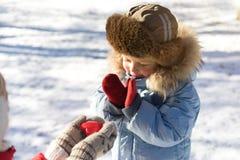拿着红色心脏室外在手套和显示对小男孩的妇女 库存照片