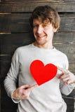 拿着红色心脏标志的年轻快乐的微笑的人 免版税库存图片