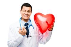 拿着红色心脏气球的亚裔医生 库存照片