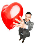 拿着红色心脏气球的商人 库存照片
