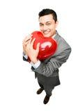 拿着红色心脏气球的商人 免版税库存图片