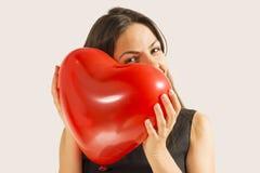 拿着红色心脏气球的妇女 免版税库存照片
