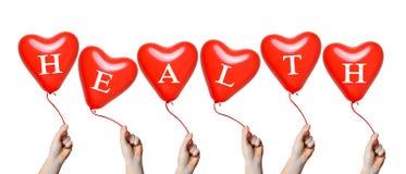 拿着红色心脏气球的手 免版税图库摄影