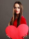 拿着红色心脏爱标志的女孩 免版税库存图片