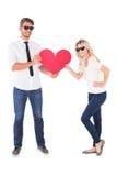 拿着红色心脏的凉快的年轻夫妇 免版税库存照片