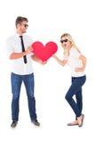 拿着红色心脏的凉快的年轻夫妇 免版税库存图片