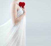 拿着红色心脏的华美的妇女 免版税图库摄影
