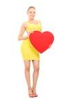 拿着红色心脏的可爱的妇女 免版税库存照片