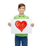 拿着红色心脏的图画或图片愉快的男孩 免版税库存照片
