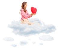 拿着红色心脏的妇女供以座位在云彩 免版税库存照片