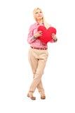 拿着红色心脏的妇女的全长画象 库存照片