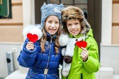 拿着红色心脏的小男孩和女孩 子项二 作为背景诱饵概念美元灰色吊异常分支 库存图片