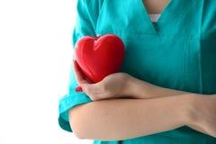 拿着红色心脏的少妇医生,在办公室 免版税库存图片