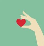 拿着红色心脏的平的手 免版税库存图片