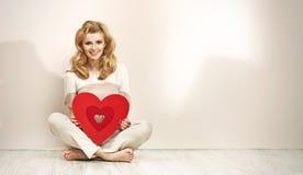 拿着红色心脏的引诱的白肤金发的女孩 免版税图库摄影