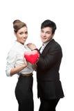 拿着红色心脏的快乐的年轻企业夫妇 免版税库存图片