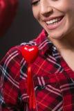 拿着红色心脏的性感和微笑的妇女 免版税库存照片