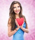 拿着红色心脏的愉快的微笑妇女。女性式样举行华伦泰 免版税图库摄影