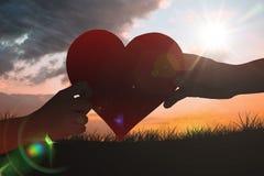 拿着红色心脏的手的综合图象 免版税库存图片