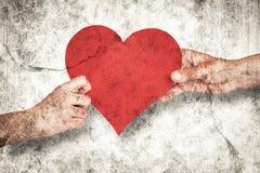 拿着红色心脏的手的综合图象 免版税库存照片