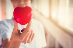 拿着红色心脏的护士手 免版税库存照片