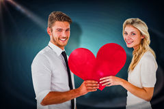 拿着红色心脏的有吸引力的年轻夫妇的综合图象 图库摄影
