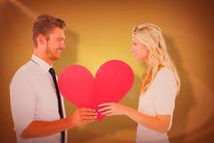 拿着红色心脏的有吸引力的年轻夫妇的综合图象 库存图片